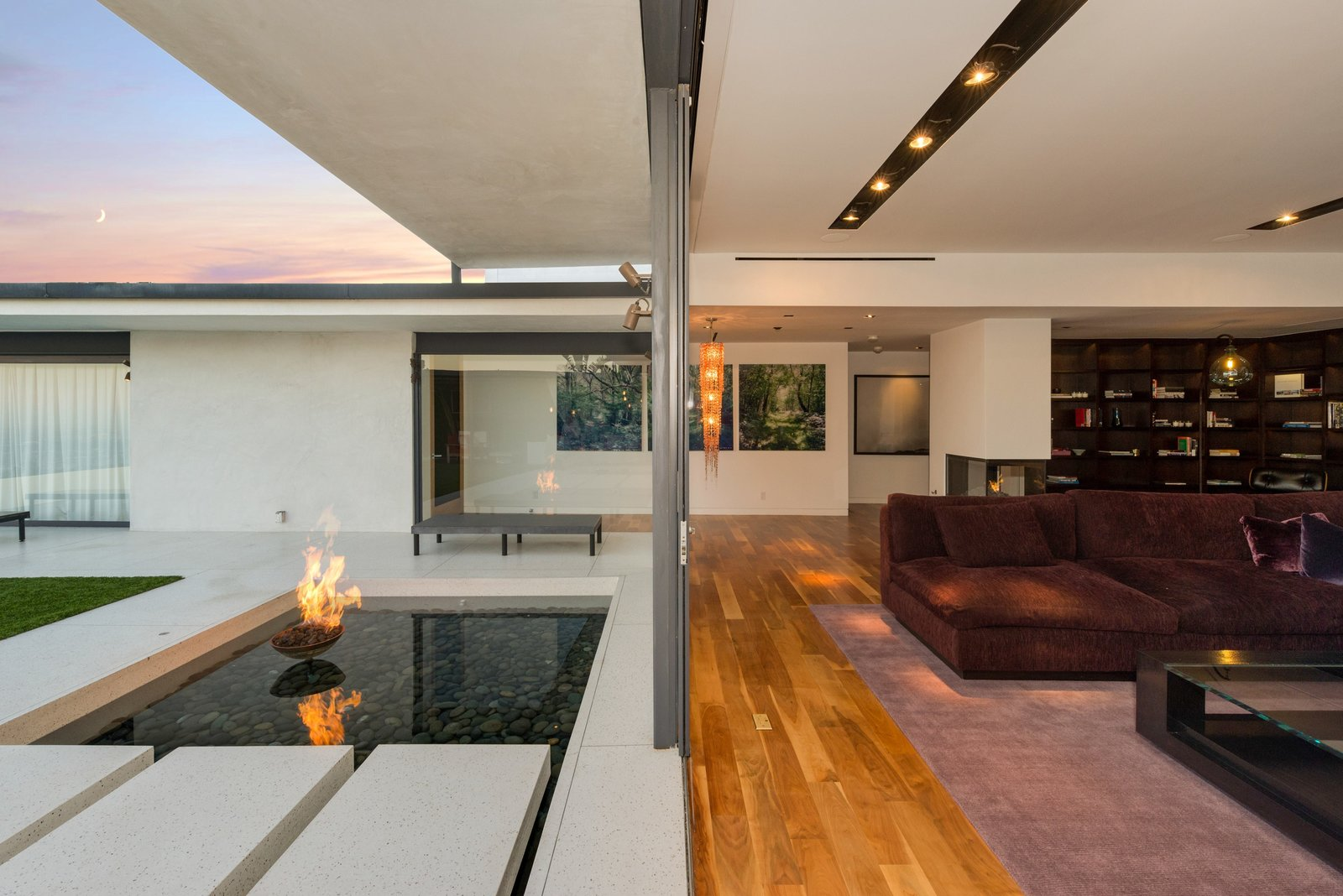 Living Room, Coffee Tables, Sectional, Medium Hardwood Floor, Ceiling Lighting, and Two-Sided Fireplace  Hopen Place