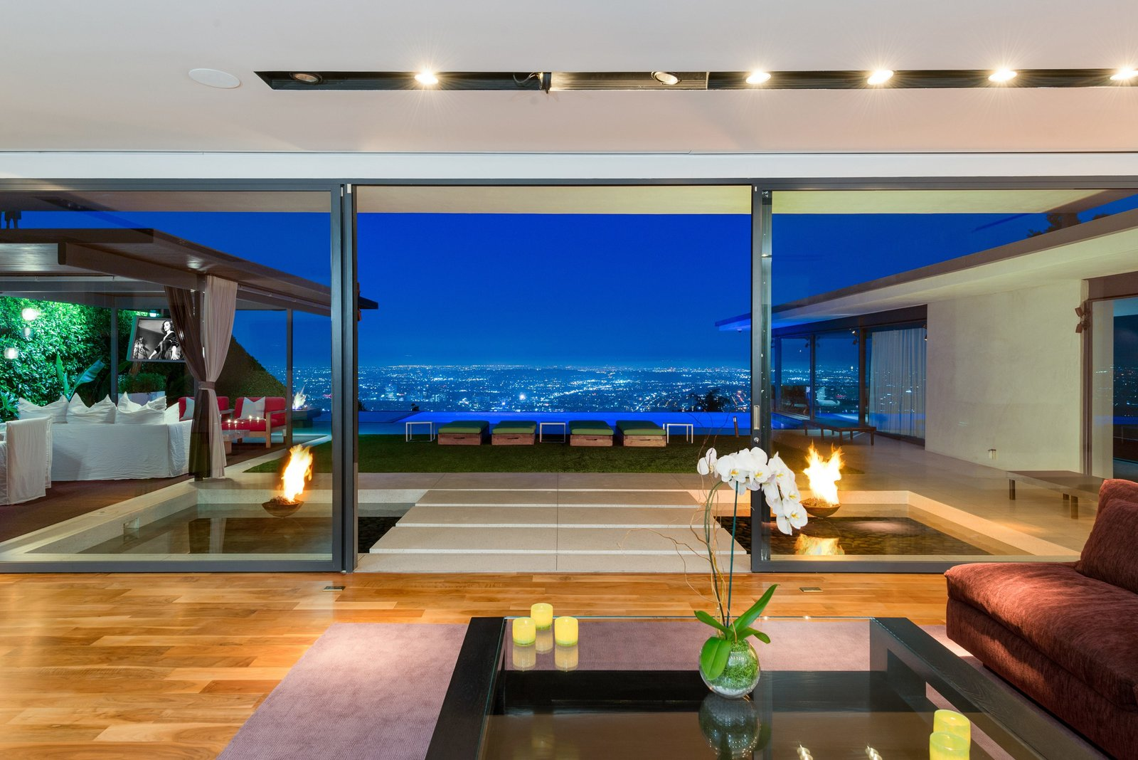 Tagged: Living Room, Ceiling Lighting, Sofa, Coffee Tables, and Medium Hardwood Floor.  Hopen Place from 'Friends' Star Matthew Perry's Midcentury Stunner in the Hollywood Hills Is For Sale