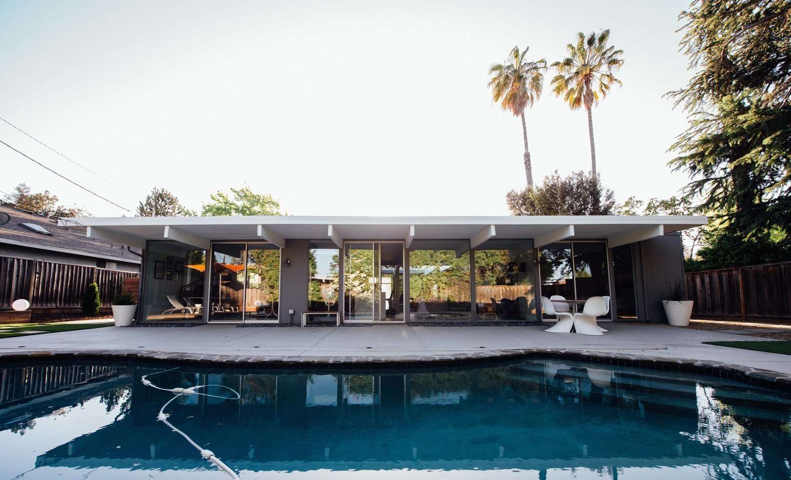 Outdoor, Trees, Back Yard, Stone Patio, Porch, Deck, Small Pools, Tubs, Shower, Wood Fences, Wall, and Swimming Pools, Tubs, Shower  Photo 2 of 11 in An Interior Designer Launches Her Career by Renovating Her Family's Midcentury Eichler