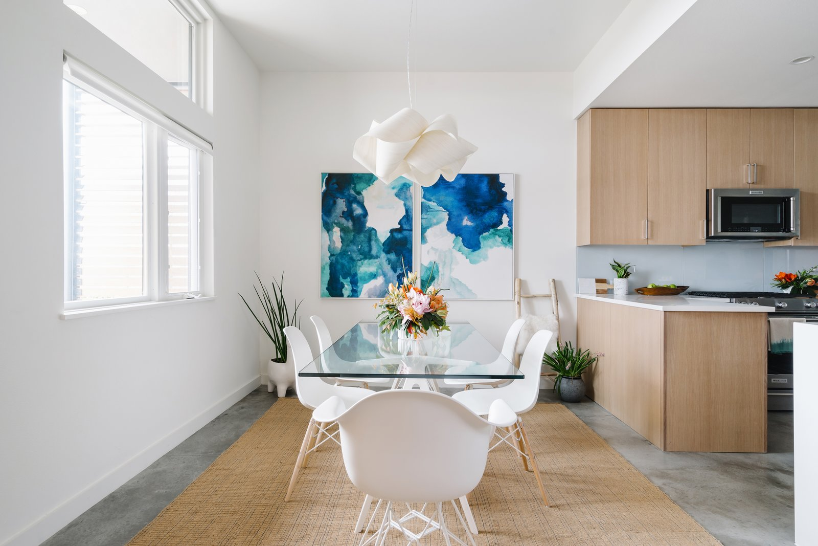 The dining room is outfitted with a pair of striking paintings by Vivian Caits. Tagged: Dining Room, Table, Pendant Lighting, and Concrete Floor.  Photo 2 of 7 in St. Barts-Inspired Accents Create Modern Tranquility in an Austin Tilley Row Home