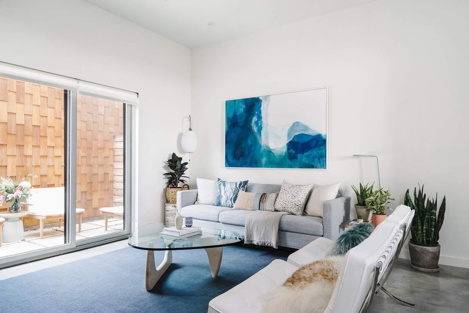 Living Room, Chair, Lamps, End Tables, Sofa, Coffee Tables, Concrete Floor, and Floor Lighting  St. Barts-Inspired Tilley Row Home from St. Barts-Inspired Accents Create Modern Tranquility in an Austin Tilley Row Home