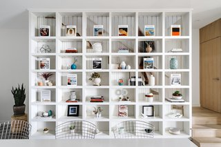 The large built-in shelving unit acts as a multifunctional divider between the dining space and the staircase.