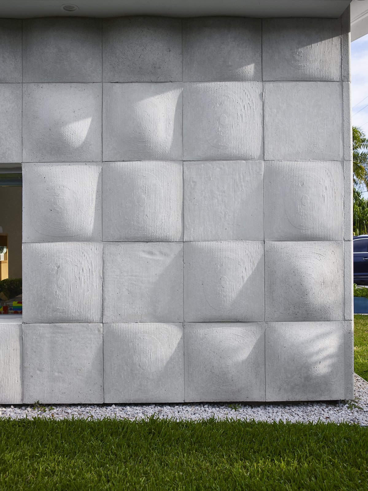 """Outdoor, Side Yard, and Grass """"For the majority of the day, when the sun is high, you almost don't notice the texture on the exterior. It just fades into a flat wash,"""" says designer Nick Gelpi of the undulating wood-based concrete tiles that clad his home in Miami Beach. """"But at moments, the sun hits at a certain angle and really activates the surface."""" - Miami, Florida Dwell Magazine : July / August 2017  Photo 2 of 12 in A Professor and Designer Tests a New Hybrid Material on His Miami Beach Home"""