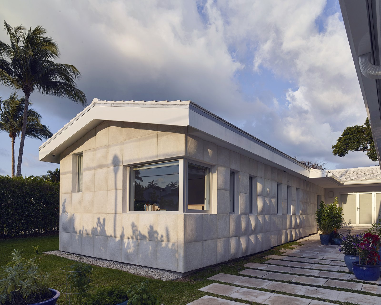 Outdoor, Shrubs, Grass, Front Yard, Raised Planters, Walkways, and Hardscapes A 450-square-foot addition reconfigured the ranch house from an  L- to a U-shape. - Miami, Florida Dwell Magazine : July / August 2017  Photo 4 of 12 in A Professor and Designer Tests a New Hybrid Material on His Miami Beach Home