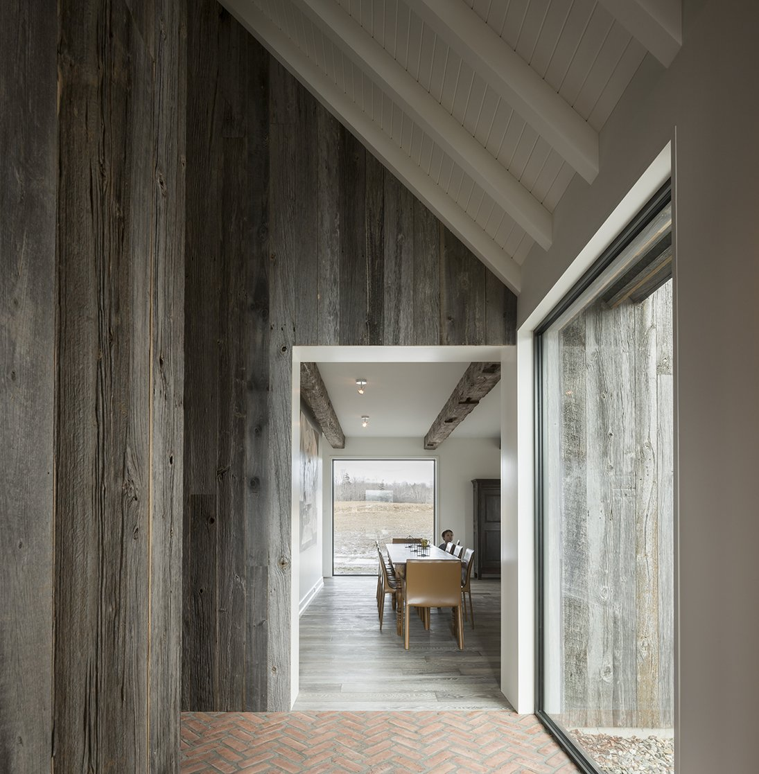 Hallway, Brick Floor, and Light Hardwood Floor Verona chairs from Structube surround a vintage dining table. - North Hatley, Quebec Dwell Magazine : July / August 2017  Photo 5 of 12 in An Artist and Farmer Work With a Toronto-Based Studio to Build a Barn-Inspired Home