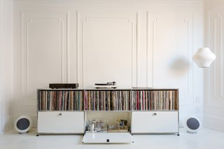 The large front parlor was turned into a music room that flows seamlessly into a long dining room. A USM credenza holds vinyl and booze. Music flows via a Pro-Ject Debut III turntable, a pair of Elipson Planet L speakers, and a Music Hall Audio amplifier.