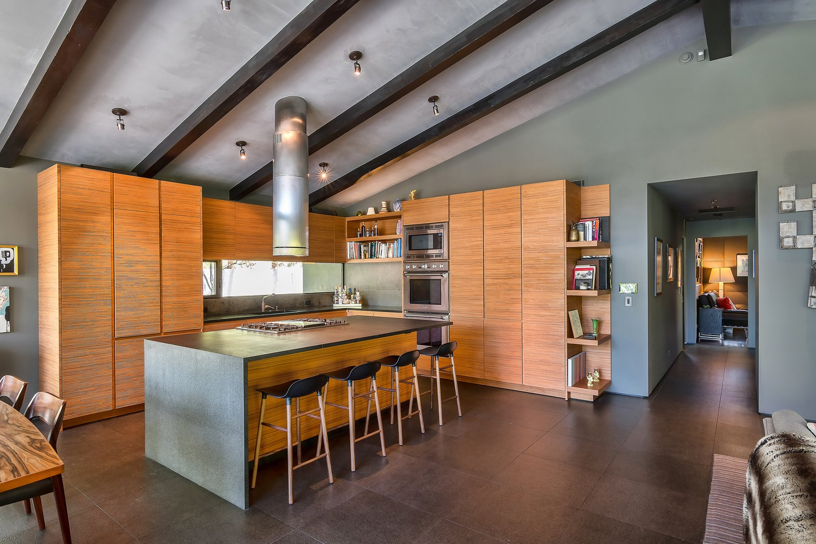 Kitchen, Wood Cabinet, Ceiling Lighting, Range, Wall Oven, Stone Counter, and Drop In Sink  Photo 6 of 14 in John Legend and Chrissy Teigen's Former Midcentury Home in the Hollywood Hills Is For Sale