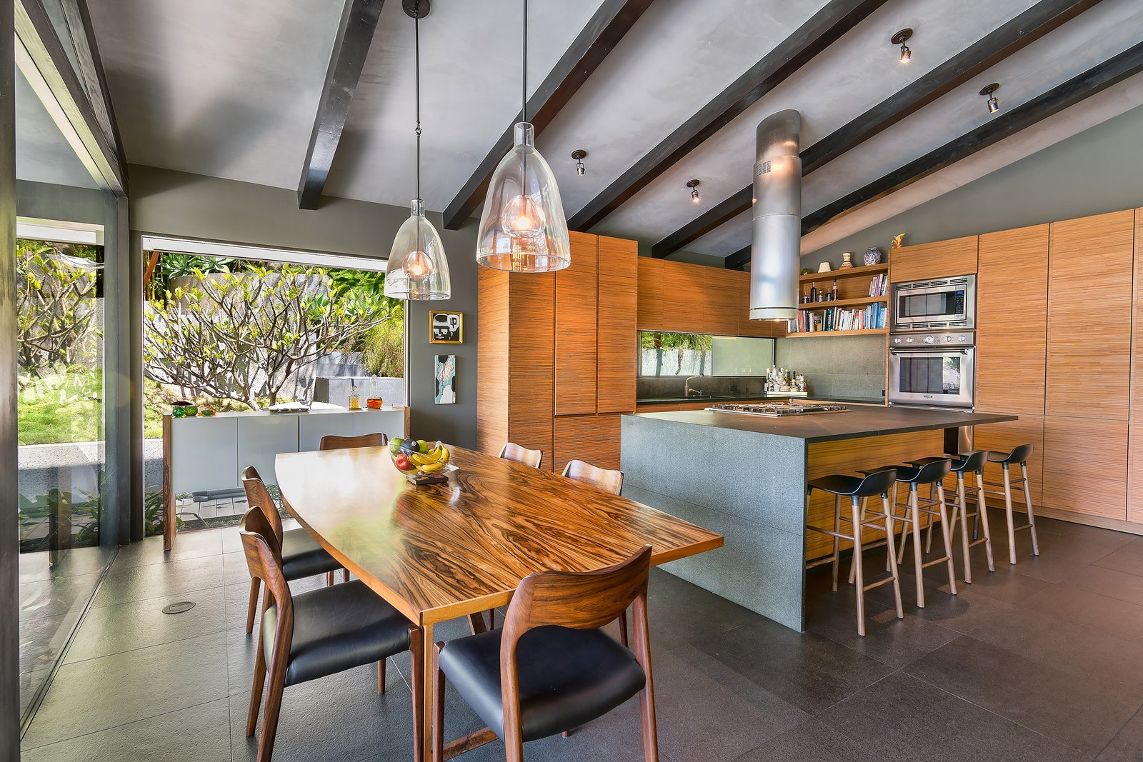Chair, Table, Pendant Lighting, Stools, Storage, Kitchen, Stone Counter, Wall Oven, Drop In Sink, Wood Cabinet, and Range  Photo 5 of 14 in John Legend and Chrissy Teigen's Former Midcentury Home in the Hollywood Hills Is For Sale