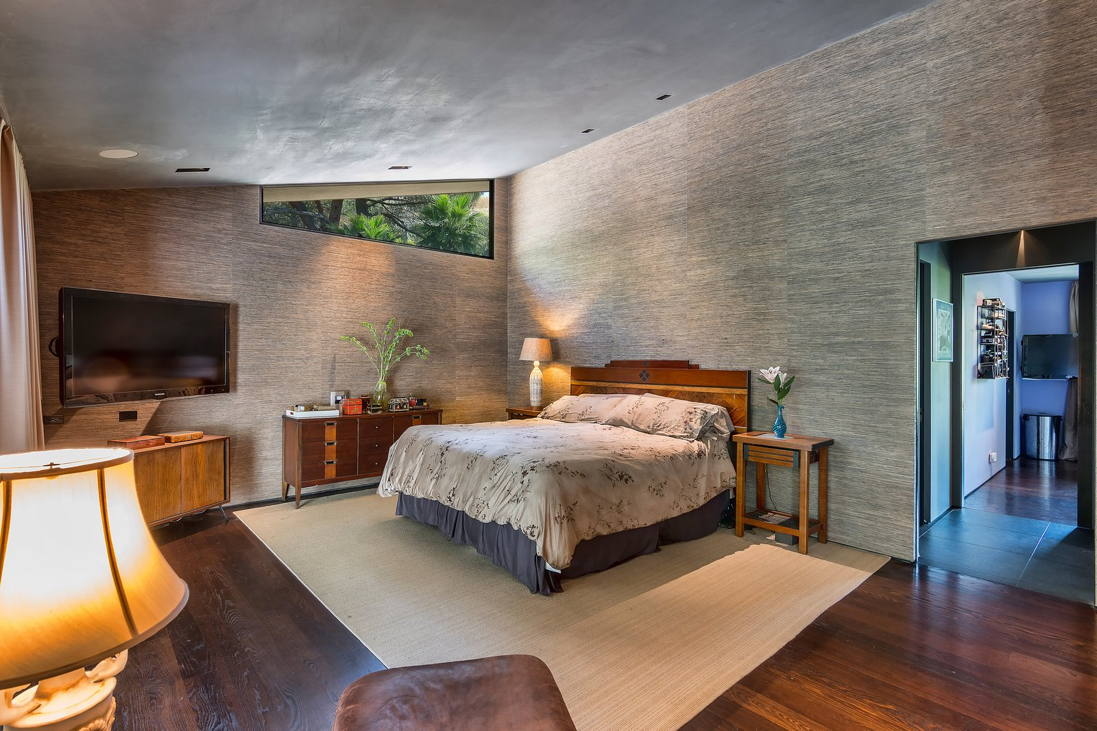 Bedroom, Recessed Lighting, Bed, Night Stands, Medium Hardwood Floor, Dark Hardwood Floor, and Dresser  Photo 7 of 14 in John Legend and Chrissy Teigen's Former Midcentury Home in the Hollywood Hills Is For Sale