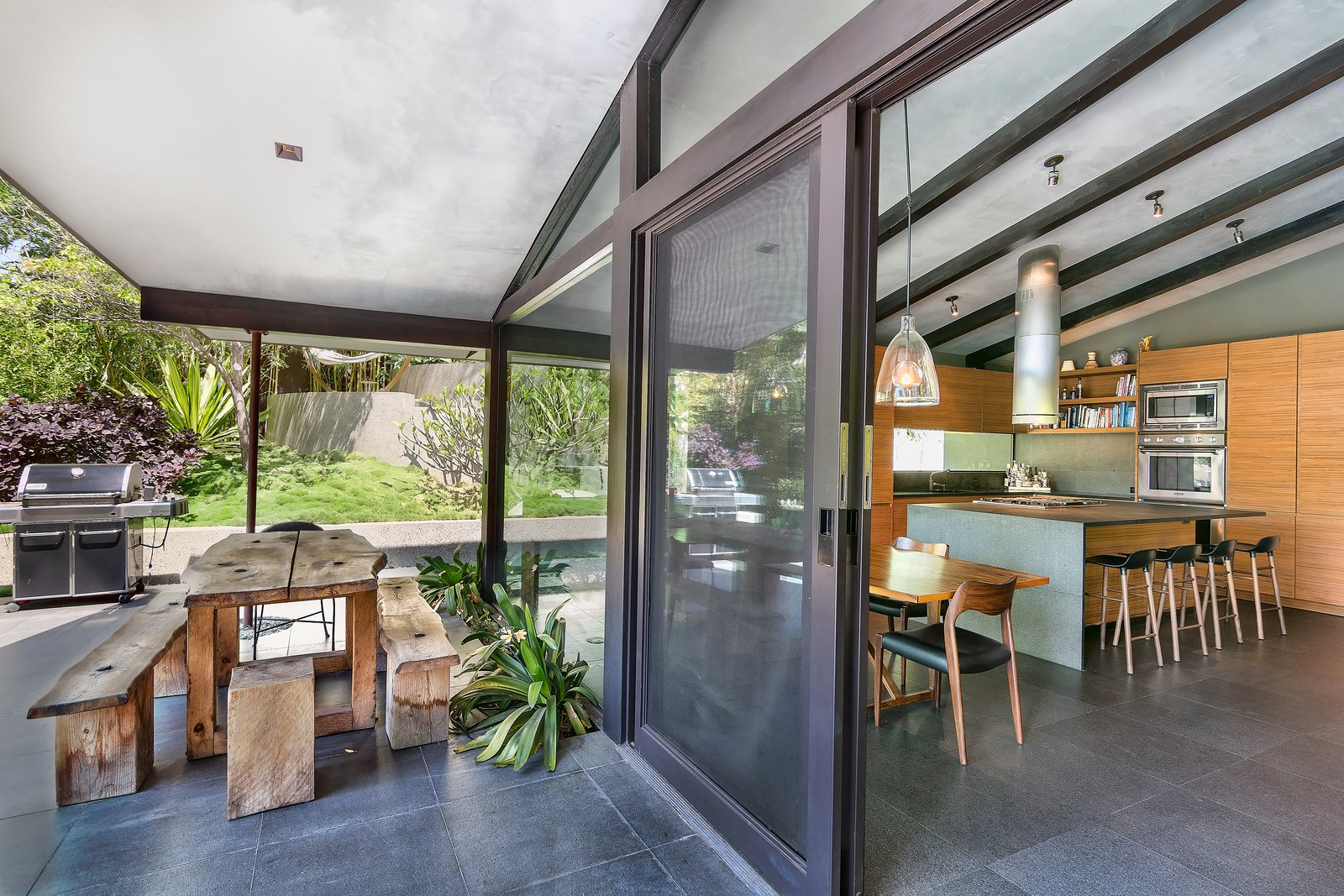 Tagged: Outdoor, Large Patio, Porch, Deck, Grass, Back Yard, and Trees.  Photo 12 of 14 in John Legend and Chrissy Teigen's Former Midcentury Home in the Hollywood Hills Is For Sale