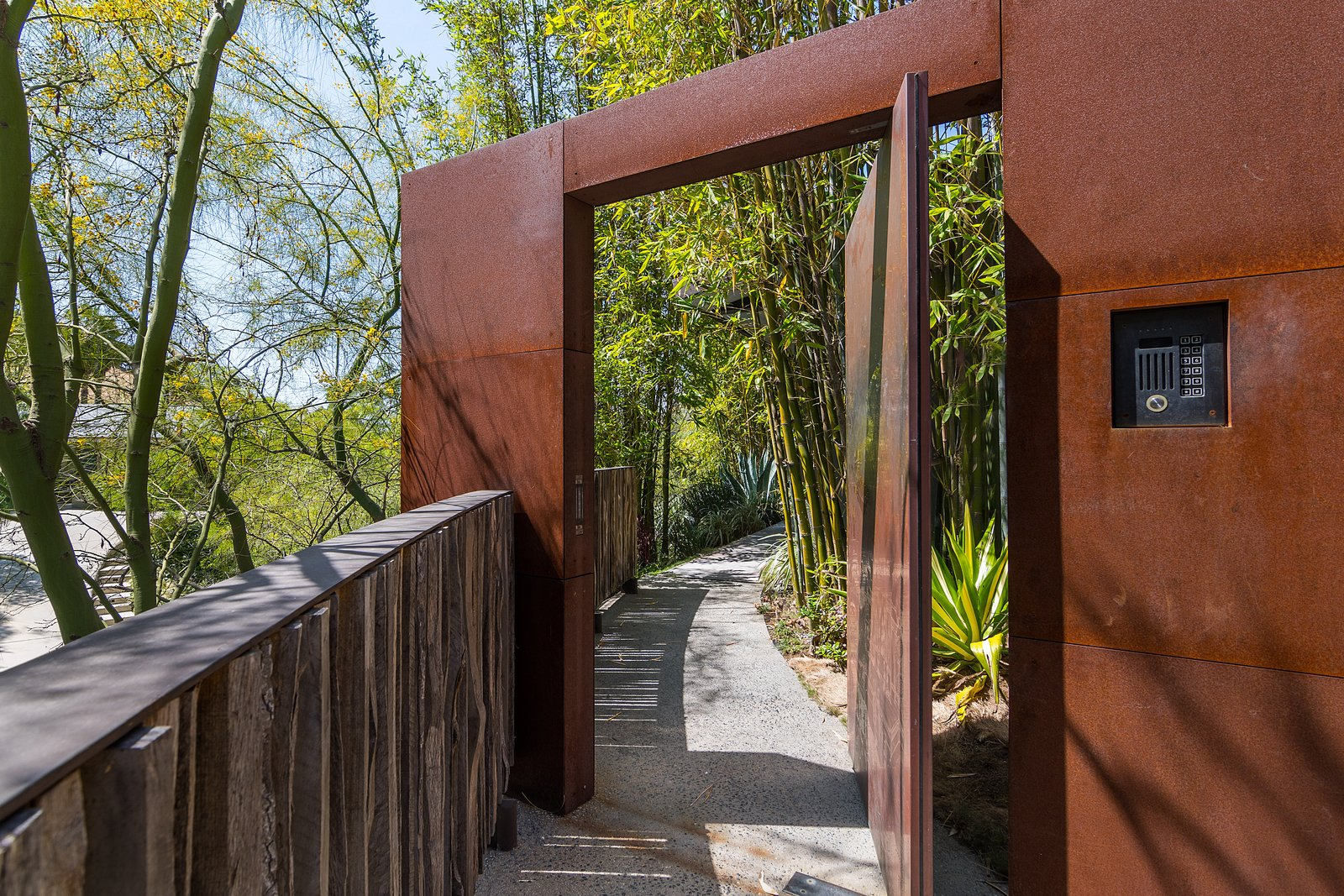 Tagged: Outdoor, Side Yard, Trees, Hardscapes, Wood Fences, Wall, and Metal Fences, Wall.  Photo 11 of 14 in John Legend and Chrissy Teigen's Former Midcentury Home in the Hollywood Hills Is For Sale