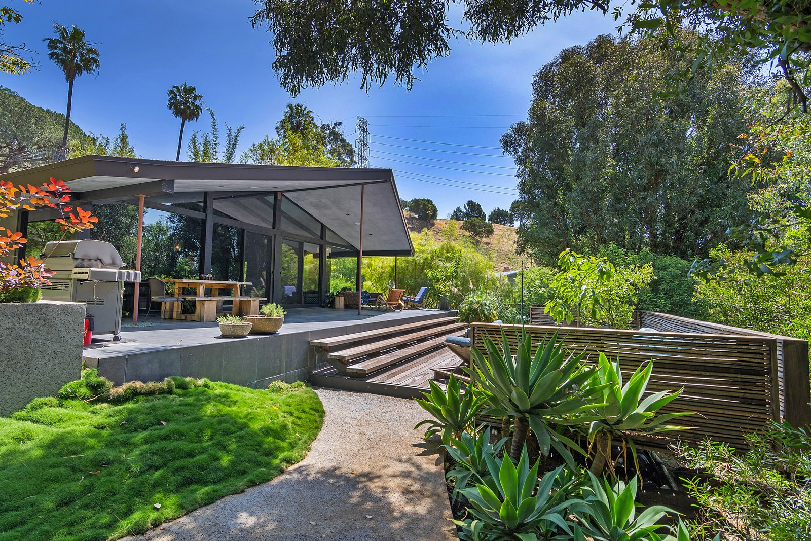 Outdoor, Horizontal Fences, Wall, Wood Patio, Porch, Deck, Large Pools, Tubs, Shower, Back Yard, Grass, Trees, Concrete Patio, Porch, Deck, and Wood Fences, Wall  Photo 1 of 14 in John Legend and Chrissy Teigen's Former Midcentury Home in the Hollywood Hills Is For Sale