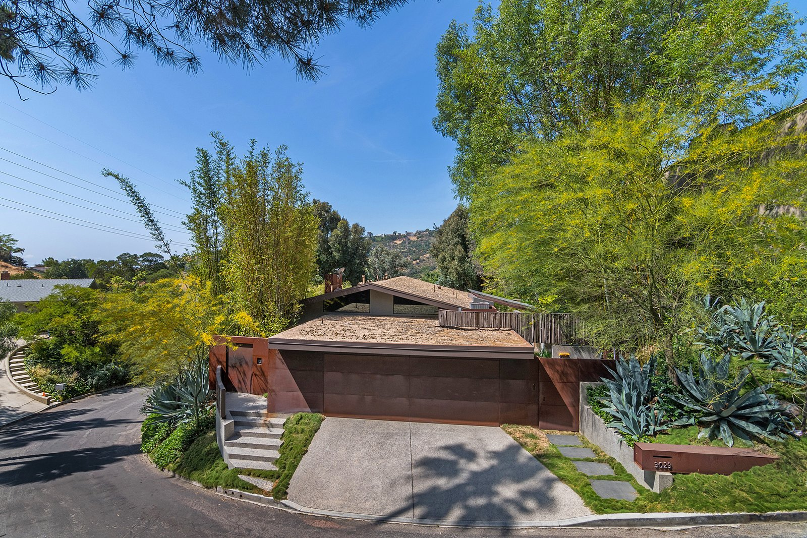 Outdoor, Trees, Front Yard, Grass, and Metal Fences, Wall  Photo 2 of 14 in John Legend and Chrissy Teigen's Former Midcentury Home in the Hollywood Hills Is For Sale