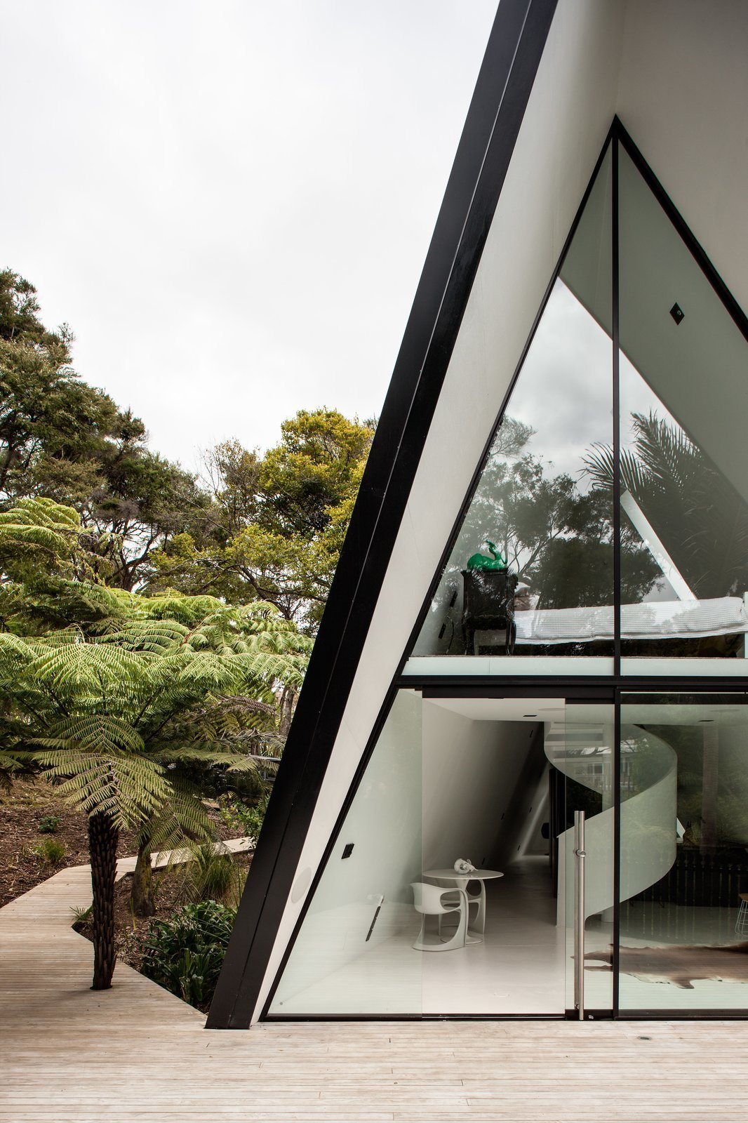 Outdoor, Front Yard, Trees, Wood Patio, Porch, Deck, and Small Patio, Porch, Deck The tent-like home responds to the challenging site in a dynamic way.  Photo 2 of 8 in Stay in a Tent-Inspired A-Frame Cabin in the New Zealand Rain Forest