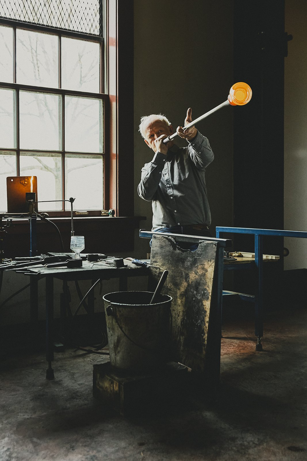 Designer Simon Pearce, shown at his factory in Windsor, Vermont, makes handblown glass the same way it's been made for thousands of years, by melting the raw ingredients in huge ovens, then gathering the molten material onto iron blowpipes. A finished Westport footed glass sits on a nearby  Photo 1 of 17 in Master Glassmaker Simon Pearce's Sustainable Factory in Vermont