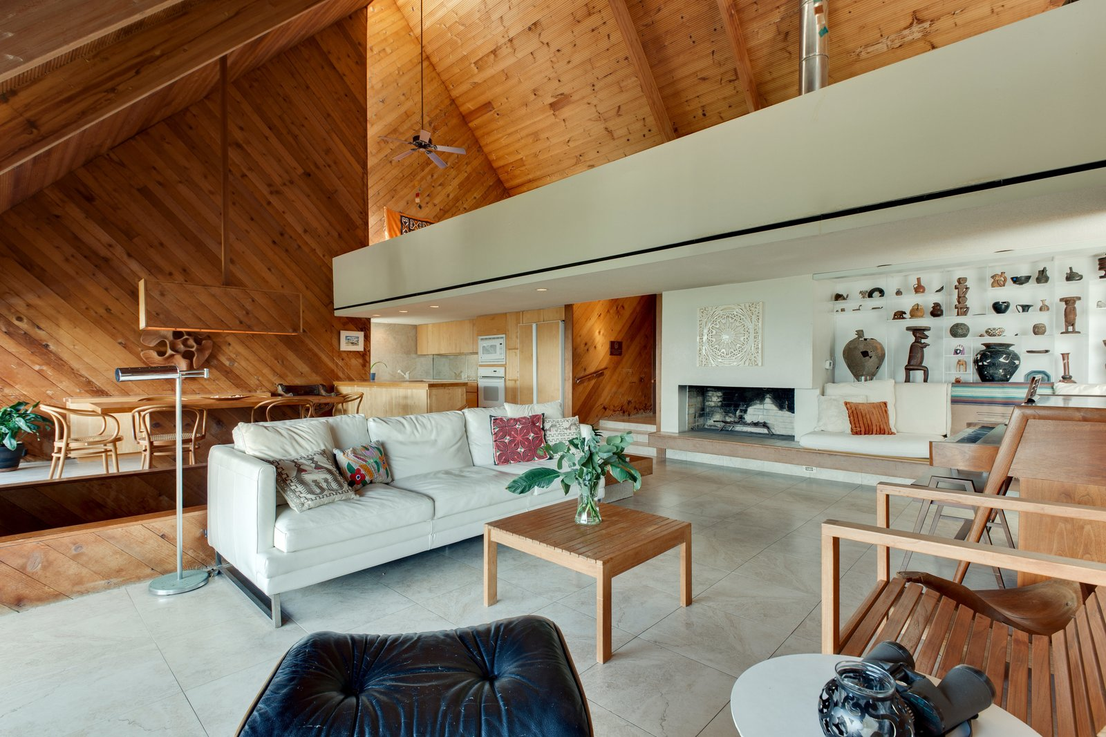 Living Room, Wood Burning Fireplace, Chair, and Sofa  Photo 9 of 13 in A Renowned Florida Architect's Geometric Family Home Hits the Market For the First Time