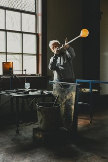 Master Glassmaker Simon Pearce's Sustainable Factory in Vermont - Photo 3 of 16 - Designer Simon Pearce, shown at his factory in Windsor, Vermont, makes handblown glass the same way it's been made for thousands of years, by melting the raw ingredients in huge ovens, then gathering the molten material onto iron blowpipes. A finished Westport footed glass sits on a nearby workstation as a point of reference.