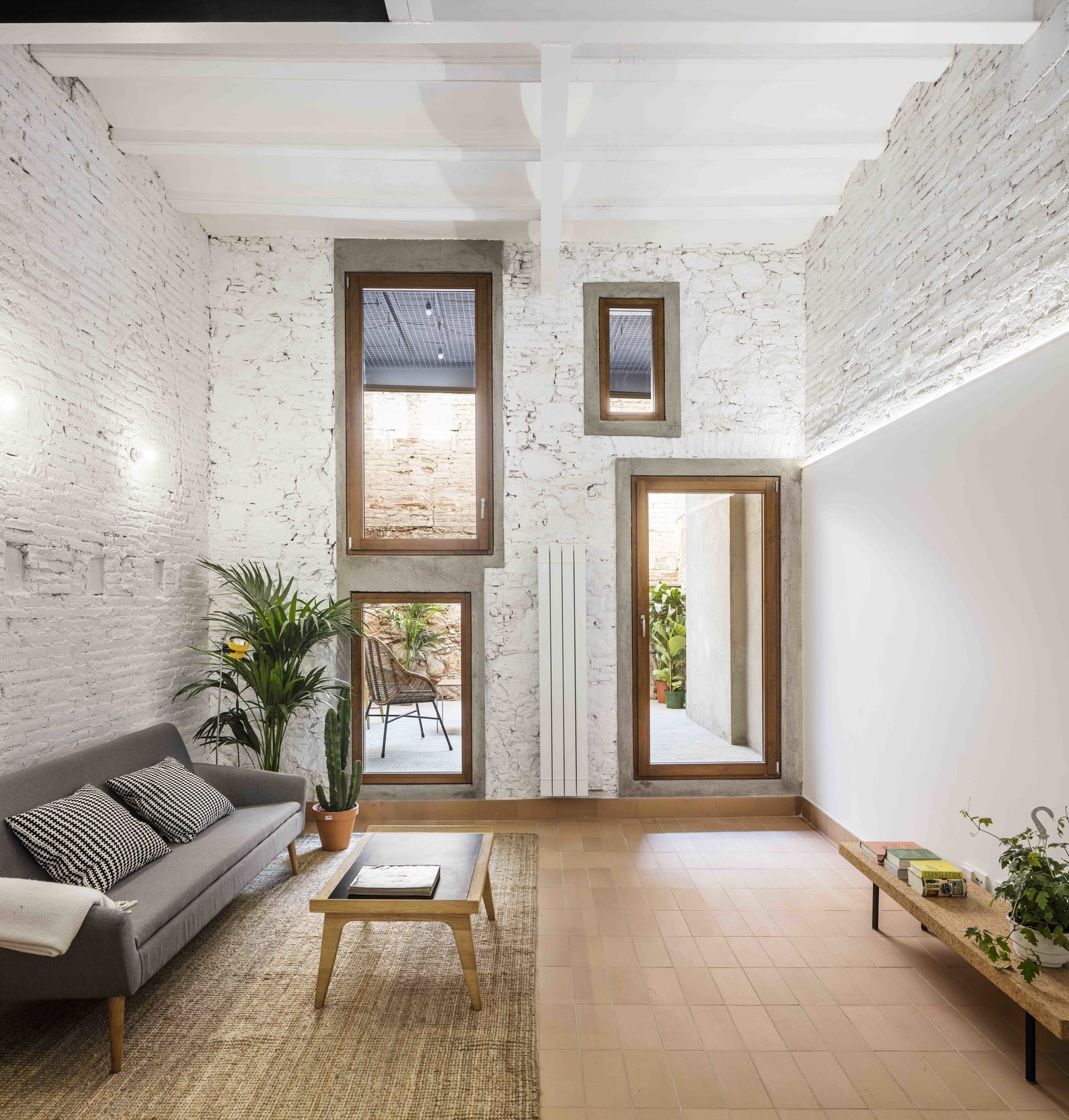 Living Room, Coffee Tables, Sofa, Bench, and Wall Lighting  Photo 10 of 13 in This Double-Height Apartment in   Barcelona Features Historic Details and a Floating Staircase