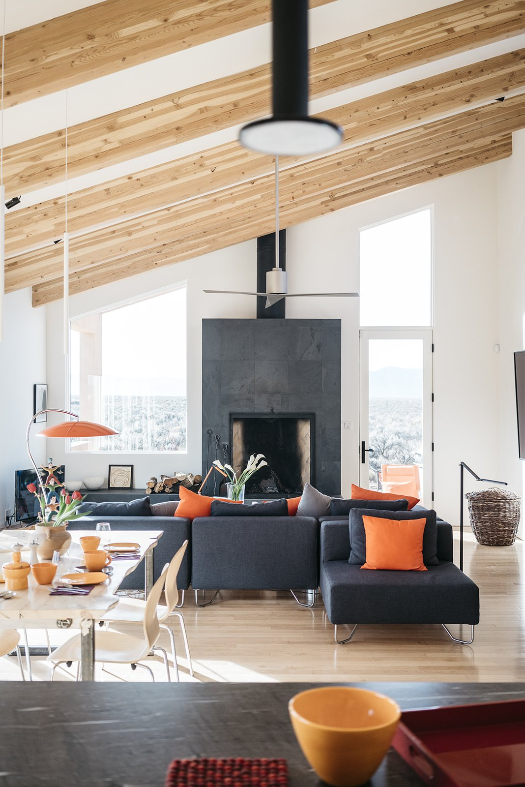 Living Room, Sectional, Table, Chair, Standard Layout Fireplace, and Table Lighting The living/dining room occupies a long, high-ceilinged space. The sectional is from CB2. - Taos, New Mexico Dwell Magazine : July / August 2017  Photo 4 of 11 in A Rookie Designer and Her Builder Father Create an Artist's Sculptural Loft in the Desert