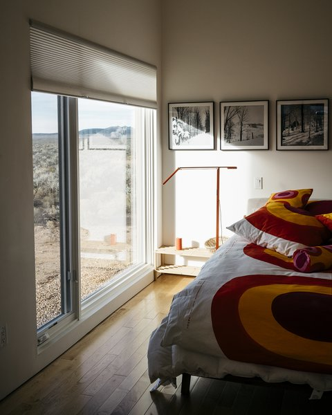 """""""It was important to Lois that the outside come inside,"""" says Molly, who designed the master bedroom to maximize the views. """"The windows make you feel like you're in a sea of sagebrush."""" The Equo Gen 3 LED floor lamp is from YLighting. - Taos, New Mexico Dwell Magazine : July / August 2017  Photo 7 of 11 in A Rookie Designer and Her Builder Father Create an Artist's Sculptural Loft in the Desert"""
