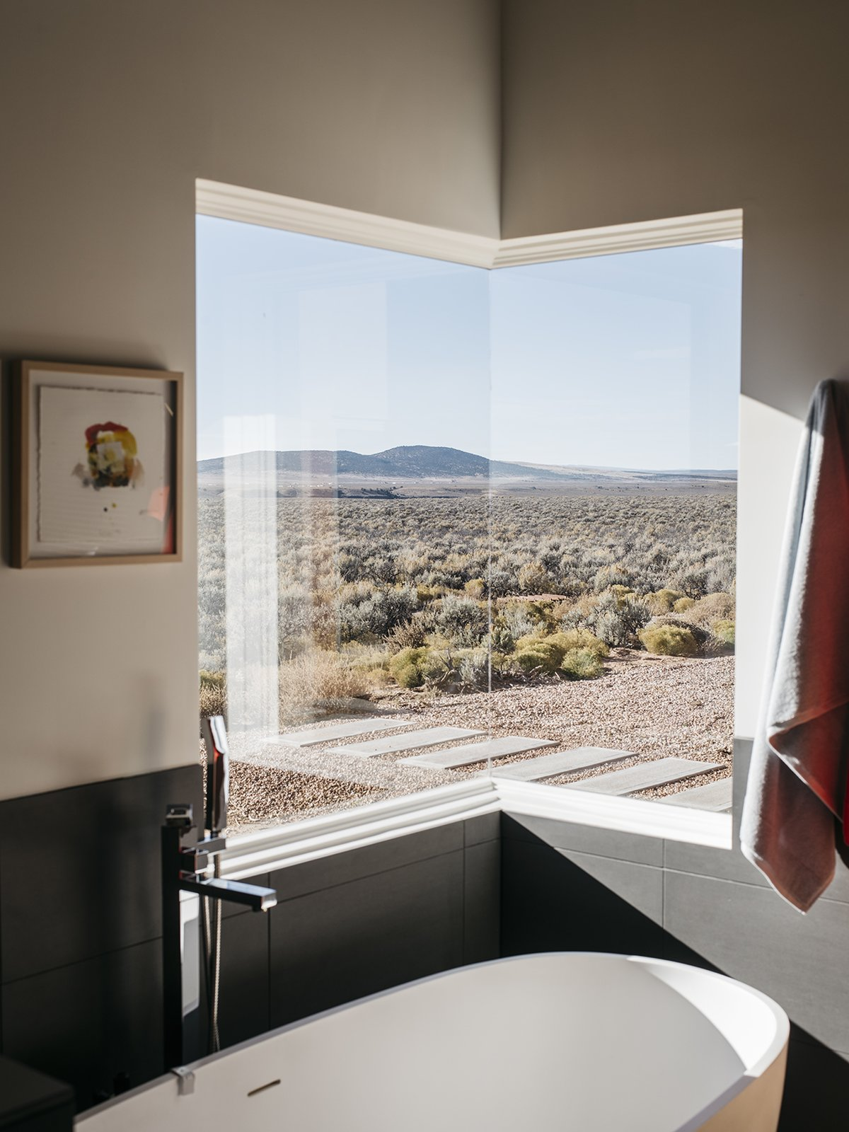 "Bath Room, Freestanding Tub, and Soaking Tub The master bathroom features one of two corner windows in the house. ""At night, when I take a bath, I can see the moon and the stars,"" says Lois. - Taos, New Mexico Dwell Magazine : July / August 2017  Photo 8 of 11 in A Rookie Designer and Her Builder Father Create an Artist's Sculptural Loft in the Desert"
