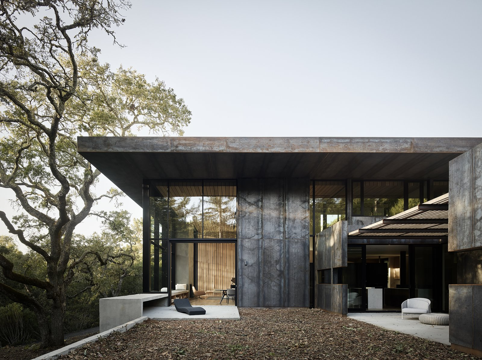 Exterior, House Building Type, Metal Roof Material, Metal Siding Material, and Flat RoofLine Located in Orinda, California, a three-bedroom house by architect Greg Faulkner took its first aesthetic cue from a large oak tree on the site. Cor-Ten steel panels clad the exterior, while white oak offers a material counterpoint on the interior. A 12-foot-wide sliding pocket wall opens the living/dining area to a terrace with a Wave Chaise longue by Paola Lenti. The landscape design is by Thuilot Associates.  Photo 2 of 14 in Nature Drove the Design of This Sculptural, Cor-Ten Steel House in Northern California