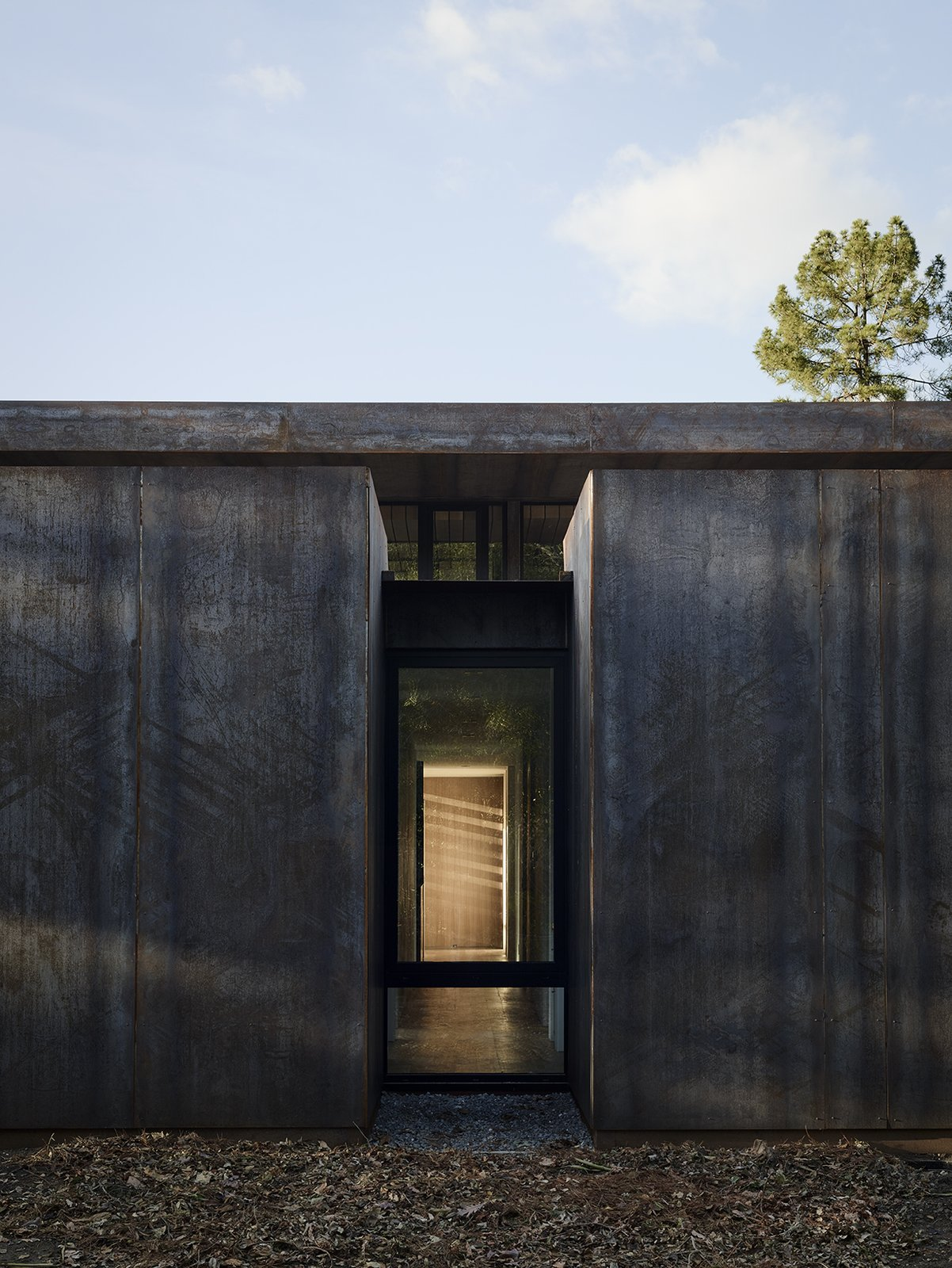 Exterior, Metal Siding Material, Flat RoofLine, Metal Roof Material, and House Building Type Overlooking the double-height living/dining area is the mezzanine level, where the master suite and office are located.  Photo 7 of 14 in Nature Drove the Design of This Sculptural, Cor-Ten Steel House in Northern California