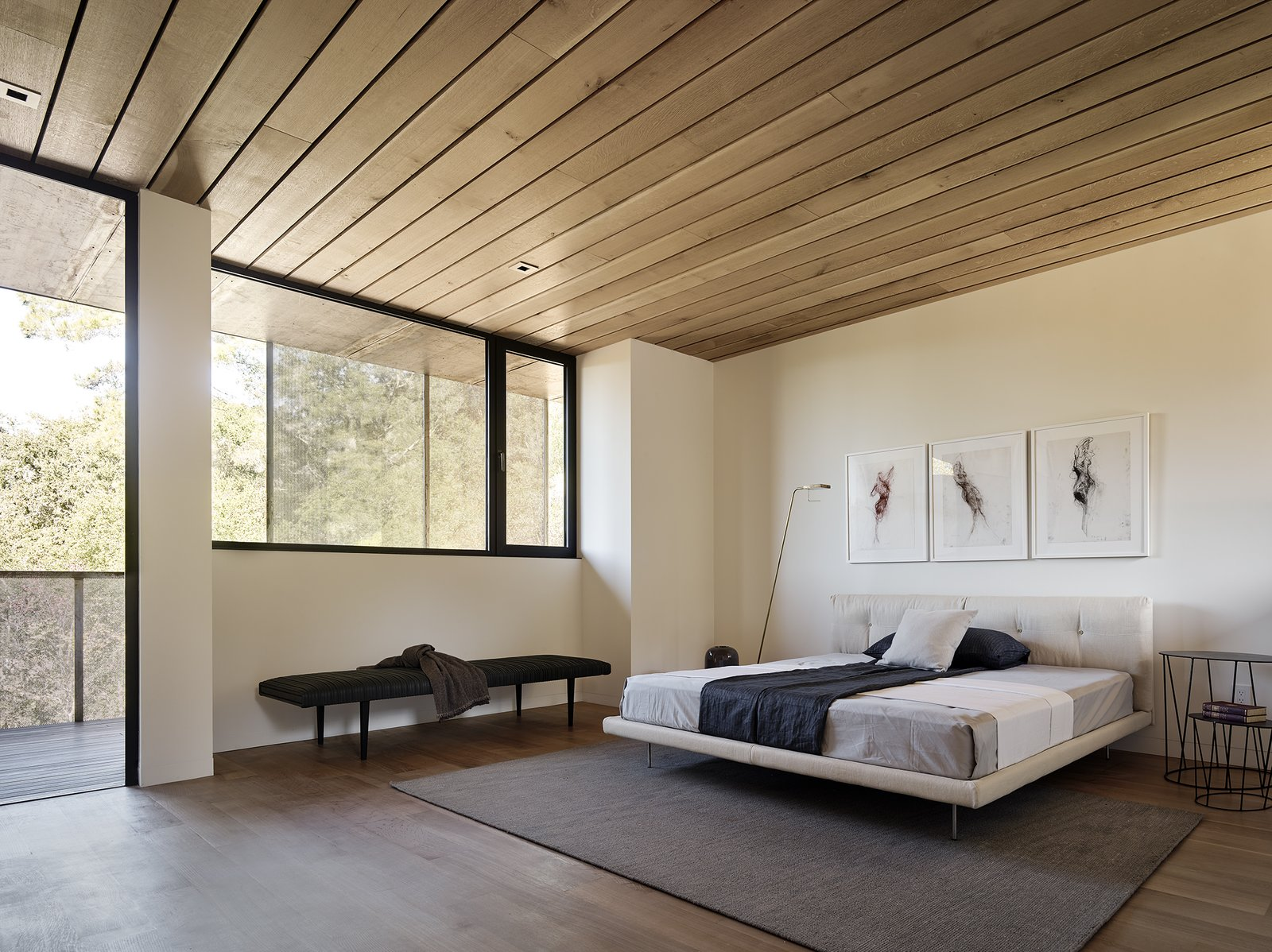 Bedroom, Bed, Medium Hardwood Floor, Lamps, Floor Lighting, Rug Floor, Bench, Night Stands, and Recessed Lighting A charcoal triptych by Gina Jacupke hangs above the Living Divani bed in the master suite.  Photo 10 of 14 in Nature Drove the Design of This Sculptural, Cor-Ten Steel House in Northern California
