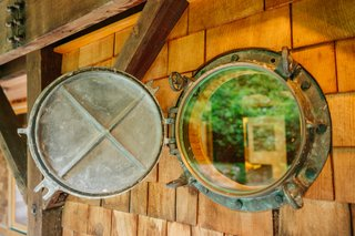 "On Bainbridge Island, just outside Seattle, architect Jason McLennan lived in this five-story home he calls his ""tree house tower."" The builders rescued touches from an old ship in a nod to the local maritime industry—such as these ship porthole windows."