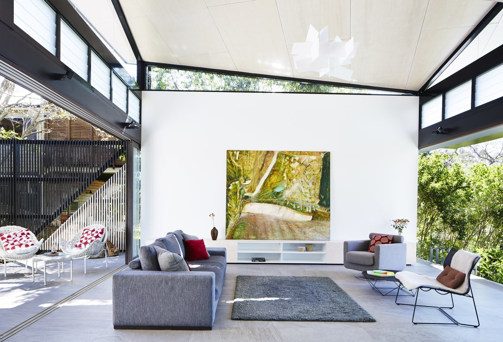 Living Room, Chair, Sofa, Storage, Bookcase, Shelves, Concrete Floor, Rug Floor, End Tables, and Pendant Lighting  Photo 4 of 12 in An Edgy Slatted Facade Conceals a Striking Indoor/Outdoor Home in Brisbane