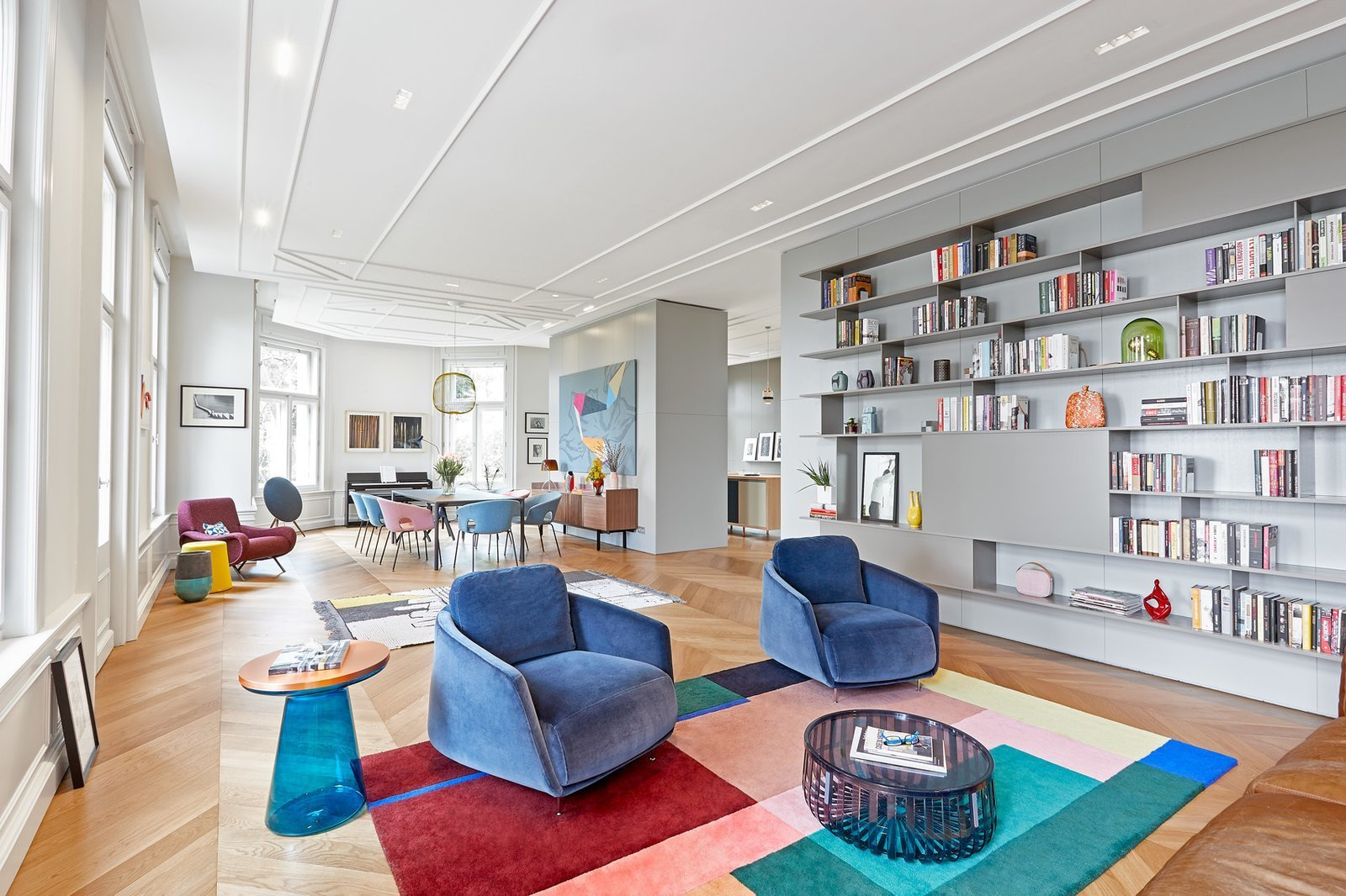Living Room, Coffee Tables, Chair, End Tables, Light Hardwood Floor, Rug Floor, Pendant Lighting, Recessed Lighting, Shelves, and Storage  Photo 2 of 17 in A Family Villa in Budapest With Colorful, 1960s-Inspired Interiors