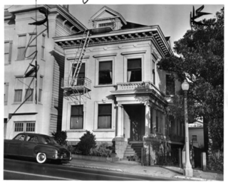 Historic photograph, 1951. Subject property is shown on the left, with the primary facade and cornice covered with stucco.