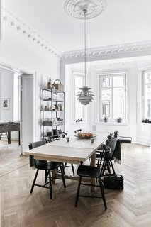 A Careful Renovation of a 19th-Century Flat in Gothenburg Brings it Back to Life - Photo 6 of 11 - A Snowball pendant by Poul Henningsen for Louis Poulsen hangs in the dining room; the J46 chairs are by Poul M. Volther.