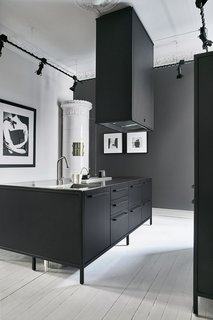 The kitchen's matte-black Vipp system is paired with an antique white ceramic tile stove that was typical in the late 19th century. Although it's not operable, the stove is used by the couple as a staging ground for illuminated candles and a storage space for an iPad that controls the home's sound system.
