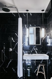 The bathroom is clad in black marble sourced from Spain.