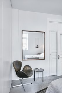 In the bedroom, a weathered Swan chair by Arne Jacobsen is next to a table designed by Vipp.