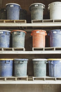 Gathering Raw Materials: Fireclay's most popular clay body is made of at least <br>55 percent recycled materials, which include postconsumer glass and granite dust. The crushed and sifted powders are stored in barrels.
