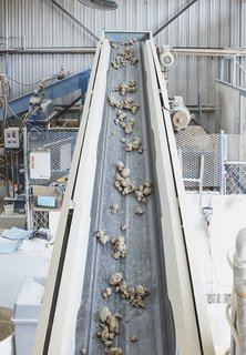 """Extrusion, Part I: Mixed clay moves on a conveyer belt to """"the Junior,"""" a 25,000-pound extruder built by the Plymouth Locomotive Company in the 1940s. It pumps out enough compressed clay each day for an estimated 2,500 square feet of tiles."""