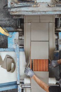 Cutting Extruded: Clay is trimmed into nine-by-nine-inch squares. The excess is sent back to the extruder by a conveyer belt, so no material is wasted.