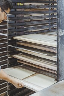 "Drying:  Damp tiles go in an industrial dryer for about 12 hours to remove excess moisture before their first firing at nearly 2,000 degrees. Once fired, tile is called ""bisque."""
