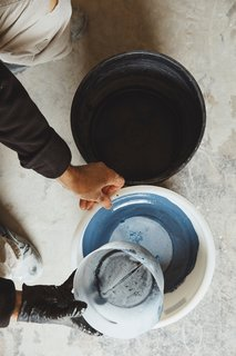 Mixing Pigments: The glaze particles—composed of silica, metal oxides, colorants, and opacifiers—are weighed, mixed, and sifted, then blended with water before they're applied to each tile.