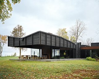 Plagued Ash Trees Were Repurposed to Create This Charred-Cedar Clad Home on Lake Michigan - Photo 1 of 9 - Desai Chia Architecture harvested plagued ash trees from the client's property and used them for interior millwork, flooring, and trim. Working in collaboration with local architect of record Ray Kendra of Environment Architects and Delta Millworks of Texas, the firm clad the dwelling's exterior in cedar that was intentionally burned to protect it from fire, insects, and age. The <br>process is called shou sugi ban.