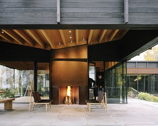 The home's undulating roof, composed of exposed wood beams and plywood sheathing, references the rolling terrain. A Cor-Ten steel–clad outdoor fireplace was built by BRD Construction; the same material was used for the interior fireplace, as surround on some windows, as cladding for the garage door, and on the chimney. The lounge chairs are from the Finn Collection from Design Within Reach. Tim Kirby of Surface Design Inc. tackled <br>the site's landscape architecture.