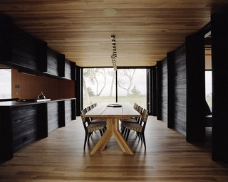 Plagued Ash Trees Were Repurposed to Create This Charred-Cedar Clad Home on Lake Michigan - Photo 8 of 9 - The dining area features an ash table designed by Desai Chia and created by Gary Cheadle. The chairs are by Jens Risom.