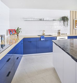 A wood countertop with blue laminate cabinets underneath contrasts with a white island topped with travertine. The wall tile is Origin Birch White by AKDO, and the brass faucet is by California Faucets. As in the rest of the apartment, the flooring is colored cork from Globus Cork.