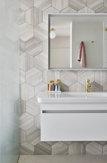 The bathroom's hexagonal marble tiles are by Ann Sacks, and the fixture, mirror, and wall cabinet are all by Duravit.
