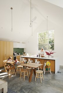 The high-ceilinged kitchen-living-dining room is outfitted with white oak casework by Henrybuilt. Leo, five, sits in a Tripp Trapp chair at a custom dining table.