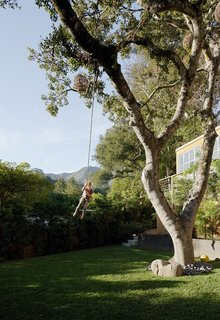Leo flies across the yard on a rope swing. The oak's trunk is surrounded by Mexican river stones. Weathered-steel planters, built by Gramajo, flank the base of the deck.
