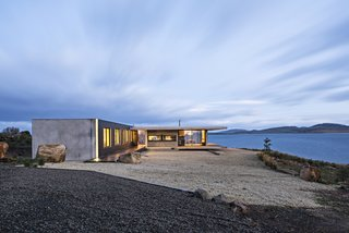 The Younger family vacation home is a semi-modular structure made of wood, steel, glass, and precast concrete. It's surrounded by Tasman gold gravel, which acts as <br>a buffer zone in case of a bushfire. A building-height LED light accentuates an exterior corner.  Styled by Julia Landgren