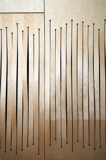 A screen of milled bent birch plywood conceals acoustical panels. Like the undulating ceiling, the screen's wave-like design helps refract sound.